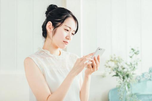 携帯を見ながら悩んでいる女性の画像